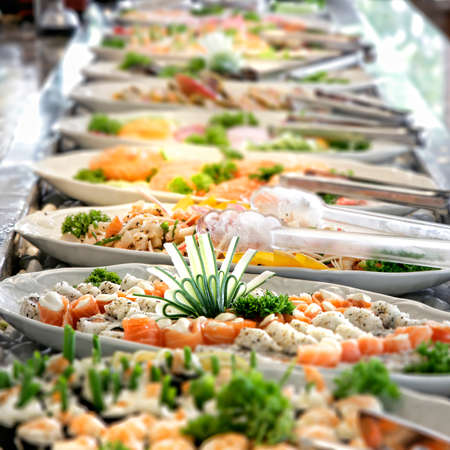 A shallow depth of field image looking along a sushi buffet bar