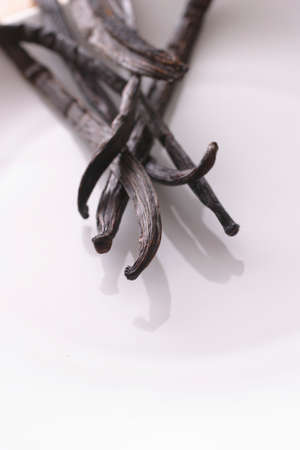 sweetening: A close up of vanilla pods on a white plate with shallow depth of field