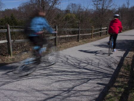 pass away: Two bicyclists in motion on the B&A trail in Millersville, MD.