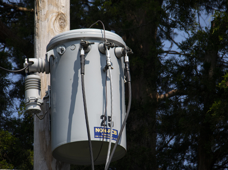 View of pole-mounted electrical transformer near rural road.