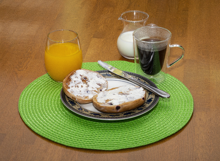 Toasted blueberry bagel breakfast with coffe and orange juice.