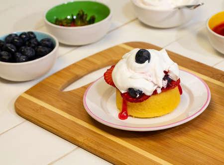 Preparing shortcake dessert with fresh strawberries, blueberries, and whipped cream.
