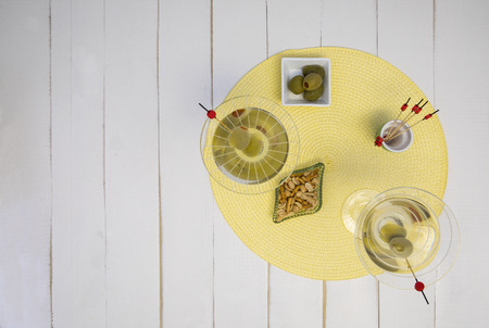 Overhead view of two mixed martinis with olives and snacks. 版權商用圖片