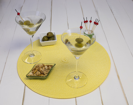 Two vodka martinis in glasses with olives and snacks on a placemat, front view.