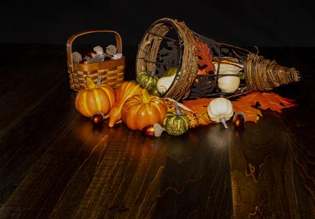 Fall harvest items are seen with decorative cornucopia on table top. 版權商用圖片