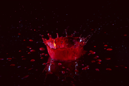 Stop action photo of water drop spashing on red liquid creating a crown effect.