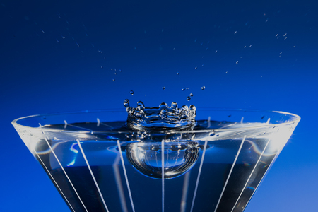 Stop motion of water drop splashing down into filled martini glass, with blue background.
