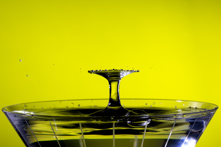 Droplets collide above martini glass, creating a radial fan pattern. Background is yellow/