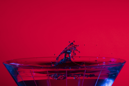 Droplets collide over a martini glass with red background and blue liquid highlights. 版權商用圖片