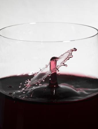 Falling wine drop collides with wine splashing in glass, creating a splash ring.