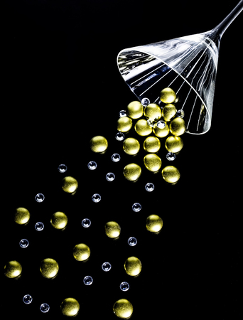 Golden nuggets and crystals spilling out of a martini glass.