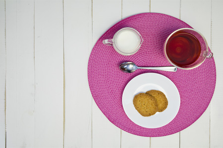Hot tea, cookies, and milk are arranged on a pink placemat on a white board table. The arrangement is off-center.