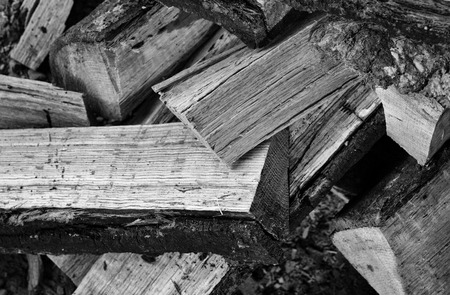 Monochrome view of a jumbled stack of cut and split oak firewood.
