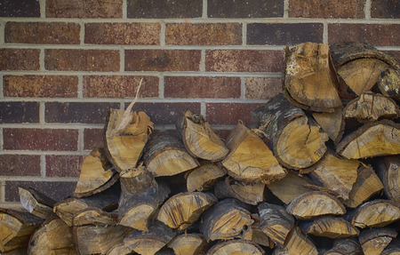 Color view of split and stacked oak firewood against a brick wall. 版權商用圖片