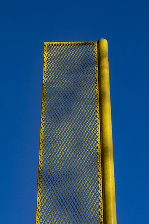 Yellow foul pole on recreational baseball field is framed against a deep blue sky.