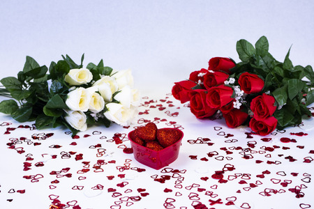 Red and white bouquets of roses with basket of hearts for Valentine's Day.