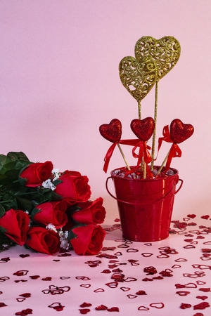 Valentine's Day scene with red roses and a bucket of decorative hearts.