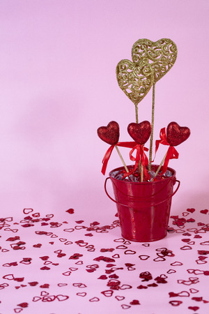 Valentine's Day bucket with red and gold decorative hearts on pink background. 版權商用圖片