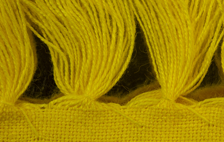 Overhead closeup view of yarn tassels along the edge of a yellow placemat. There is a repeating pattern of tassels. 版權商用圖片
