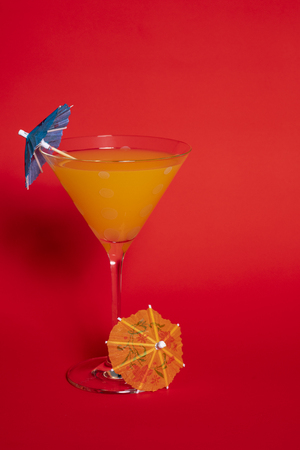 Orange drink with a blue umbrella in a martini glass set against a solid red background. An orange umbrella lies at the base of the glass.