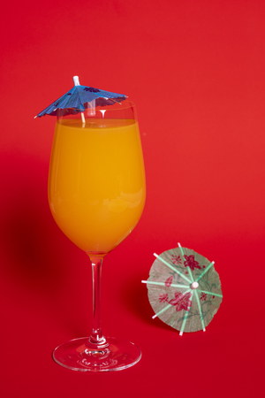 Orange drink with a blue umbrella in a wine glass set against a solid red background. A green umbrella lies beside the glass.