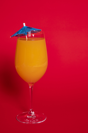 Orange drink with a blue umbrella in a wine glass set against a solid red background.