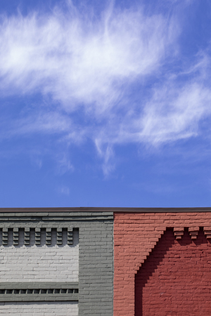 Decorative brickwork is seen along the rooflines of buldings against cirrus clouds. 版權商用圖片