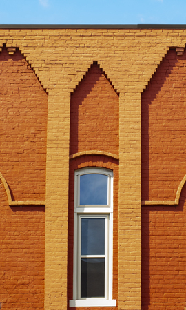 Detailed brickwork on the facade of a colorful brick building in s small town.