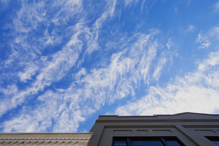 Cirrus clouds against a deep blue sky above old brick buidlings. 版權商用圖片