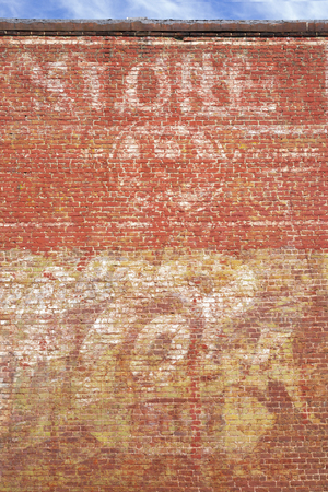 The faded paint of old advertising seen on the side of a brick building in a small town. 版權商用圖片