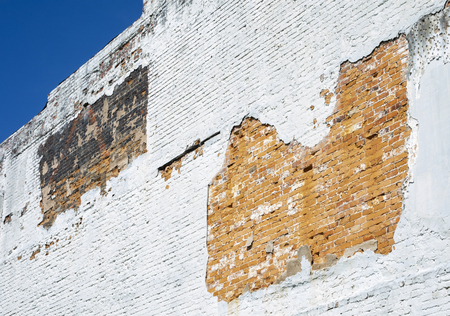Nature has worn away some plaster revealing the underlying brick on this old building.