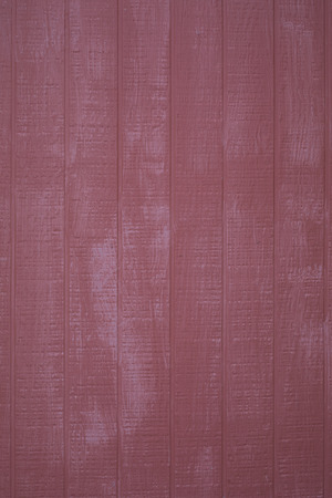 Exterion red barn wall, vertical planking, vertical format;
