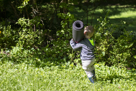 Male toddler carries rolled up mat through the grass. 版權商用圖片 - 126468867