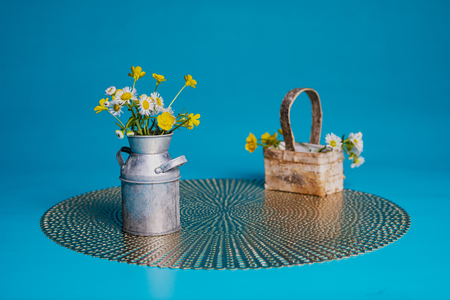 Hairy buttercup and prairie fleabane wildflowers in a miniature milk can and backet. Sitting on a placemat against a teal blue background.