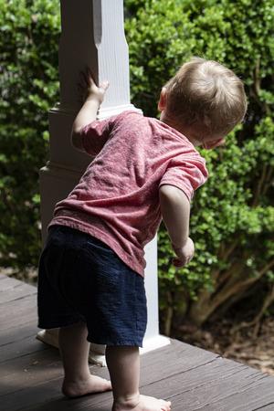 Barefoot male toddler peers around post on wooden porch. 版權商用圖片 - 126457220
