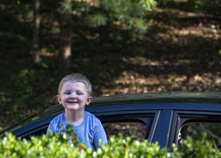 Toddler Jack stands up in car window to peer over shrubs.