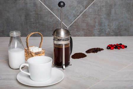 Coffee berries, beans, and grounds shown on counter with brewing French press coffee.