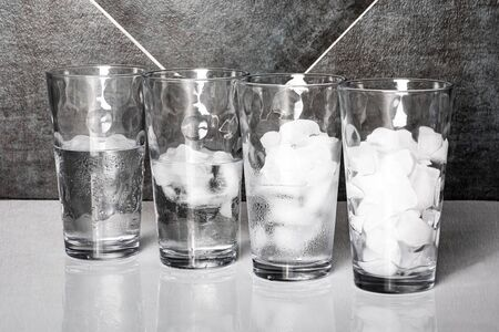 View of four glasses of ice on a table top, each at a different stage of melting. 版權商用圖片 - 142622890