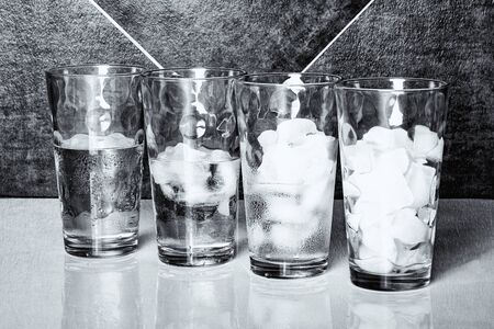 Monochrome view of four glasses of ice on a table top, each at a different stage of melting.