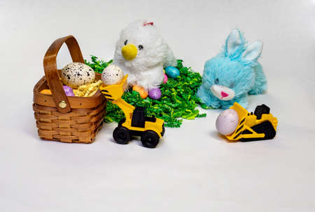 Easter themed photo of stufed bunny and hen with decorated Easter eggs, a basket,  and a child's toy construction vehicles. 版權商用圖片 - 152334804