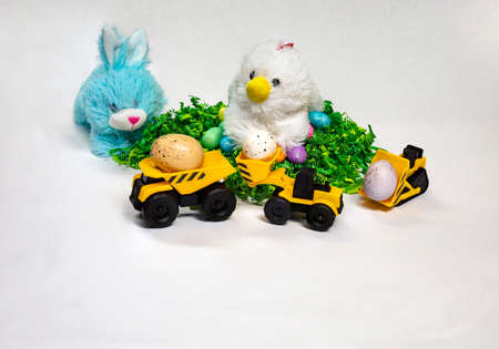 Easter themed photo of stufed bunny and hen with decorated Easter eggs and a child's toy construction vehicles. 版權商用圖片 - 152334985