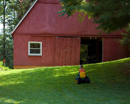 His work done for the day, a young boy drives his toy tractor toward a red barn. 版權商用圖片