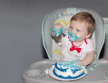Toddler celebrating first birthday with smash cake. 版權商用圖片