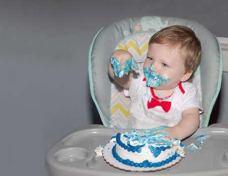 Toddler celebrating first birthday with smash cake. 版權商用圖片 - 153470954
