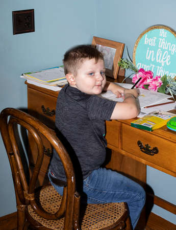 Four-year old pre-kindergarten boy works at his 'school' desk at home during COVID-19 remote class session.