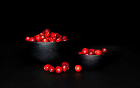 A bunch of cranberrries in 2 black, cast iron bowls, with black background. Shot in low key style.