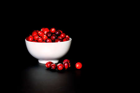 A bunch of cranberrries in a white porcelain bowl, with black background. Shot in low key style. 版權商用圖片