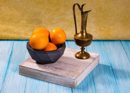 A group of oranges in a concrete geodesic bowl and a etched brass urn on a cyan base with light yellow-orange backdrop.