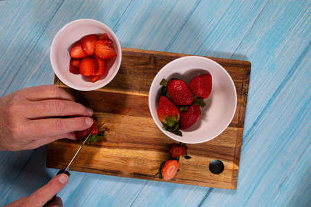 Overhead view of a man slicing plump strawberries on a wooden cutting board.