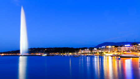 Beautiful view of the Swiss national landmark - Jet d'eau at night. To the right is the left bank of Geneva, a neighborhood called Eaux-Vives, which translated means living waters.
